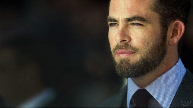 Молодой мужчина с бородой в костюме с сиреневой рубашкой