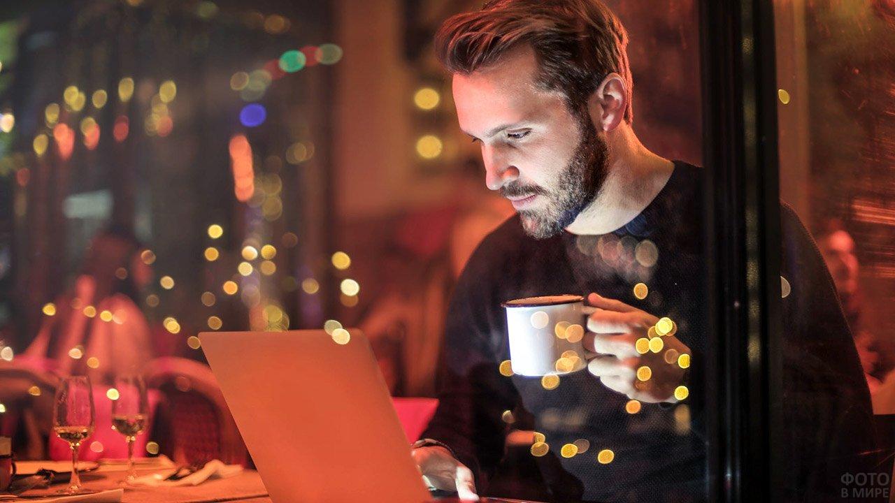 Мужчина с бородой за ноутбуком в вечерней кофейне