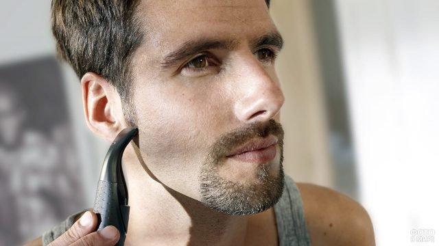 Мужчина триммером выбривает себе бороду-эспаньолку