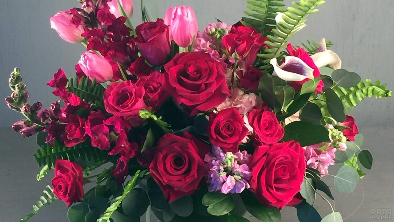 Ярко-красные розы, фрезии и тюльпаны в букете с пышной зеленью