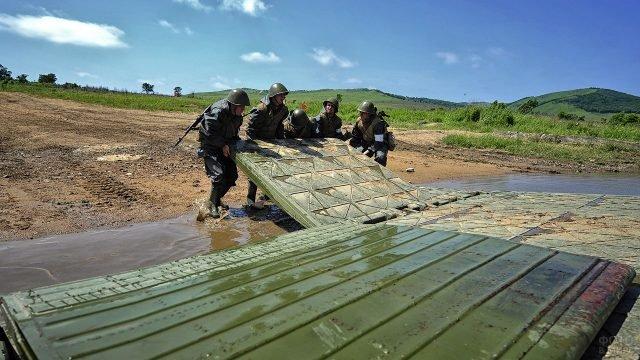Служащие Инженерных войск монтируют элементы понтонного моста