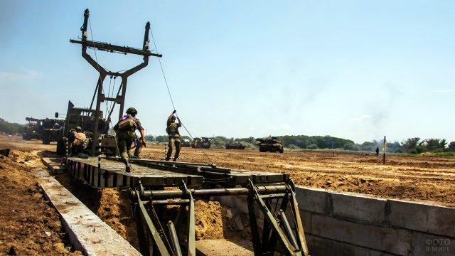 Солдаты Инженерных войск устанавливают тяжёлый механизированный мост ТММ-3