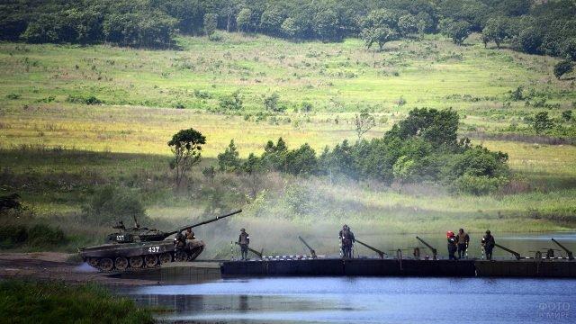 Танк въезжает на понтонный мост в сопровождении служащих Инженерных войск
