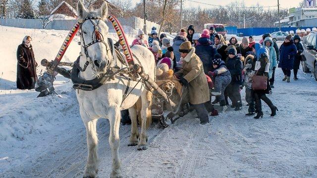 Дети садятся в запряжёные сани на рождественских гуляниях в Коломне