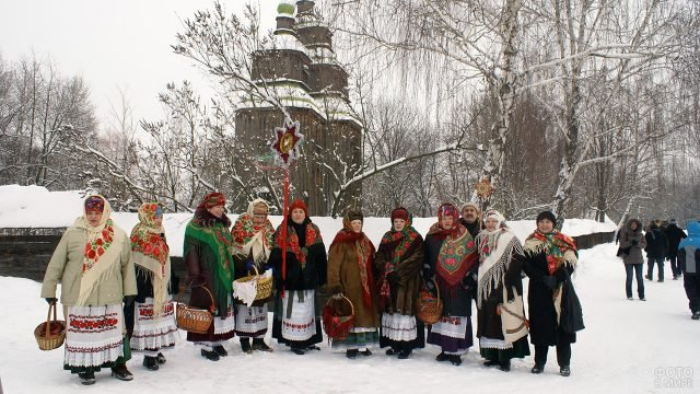 Колядующие христославы в народных костюмах посреди заснеженной аллеи