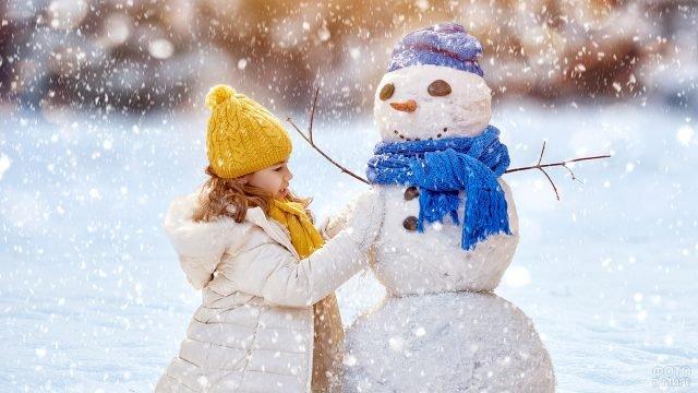 Девочка лепит снеговика в синем шарфе под лёгким снегопадом