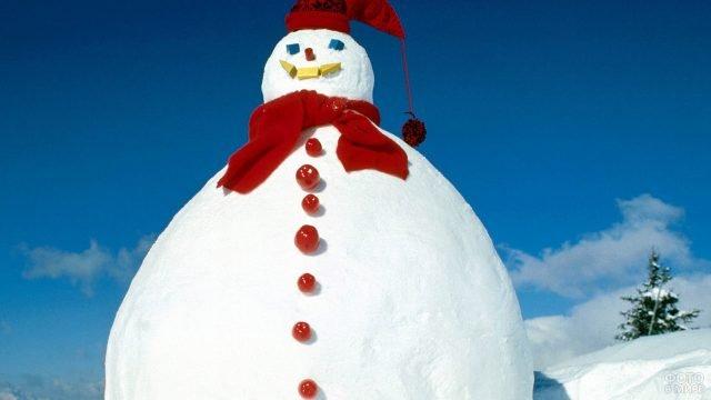 Гигантский снеговик в красных шапочке и шарфе