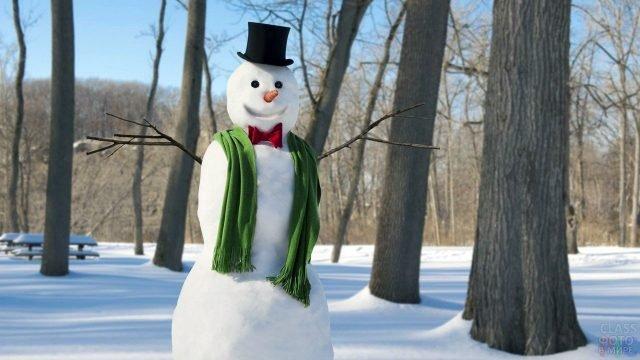 Красивый снеговик в цилиндре, бабочке и шарфе-кашне в зимнем парке