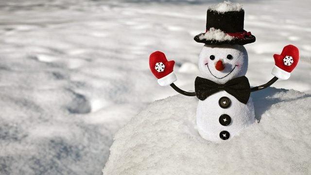 Снеговичок из носка в рукавичках, шляпе и галстуке-бабочка в снежном сугробе
