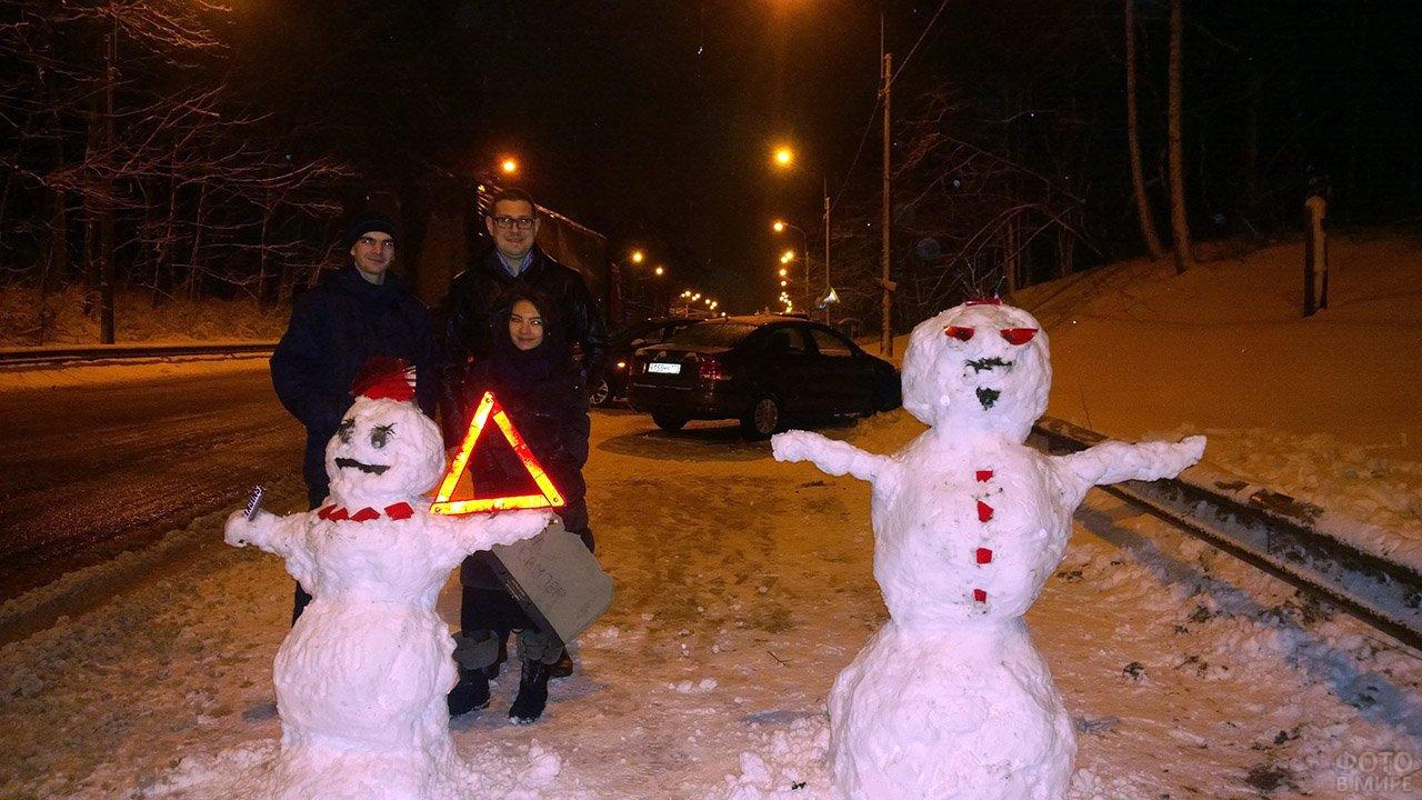 Снеговики с аварийкой на вечерней обочине