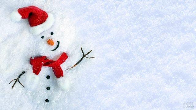 Утонувший в снегопаде снеговик в шапочке и шарфе