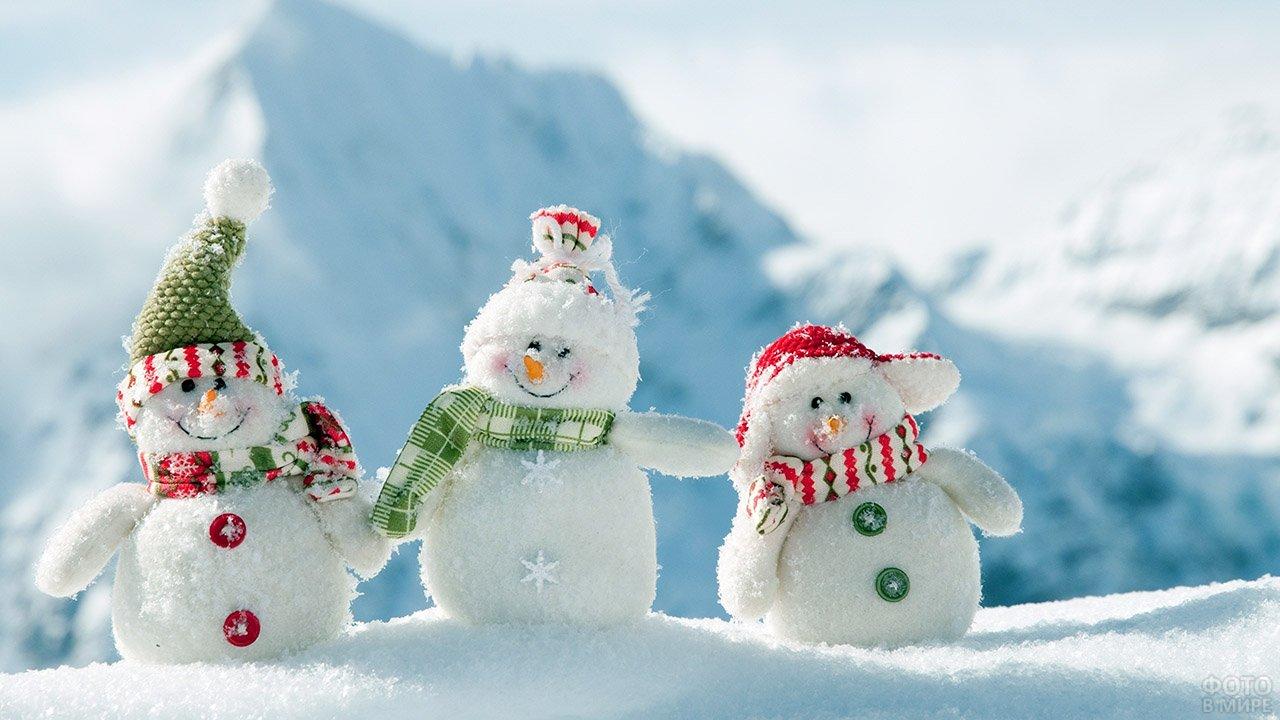 Забавные снеговички в шапочках-колпачках в сугробе на фоне гор