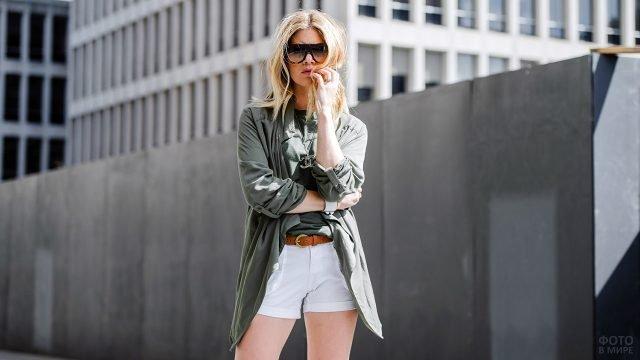 Девушка в белых мини-шортах и топе с кофтой в стиле милитари