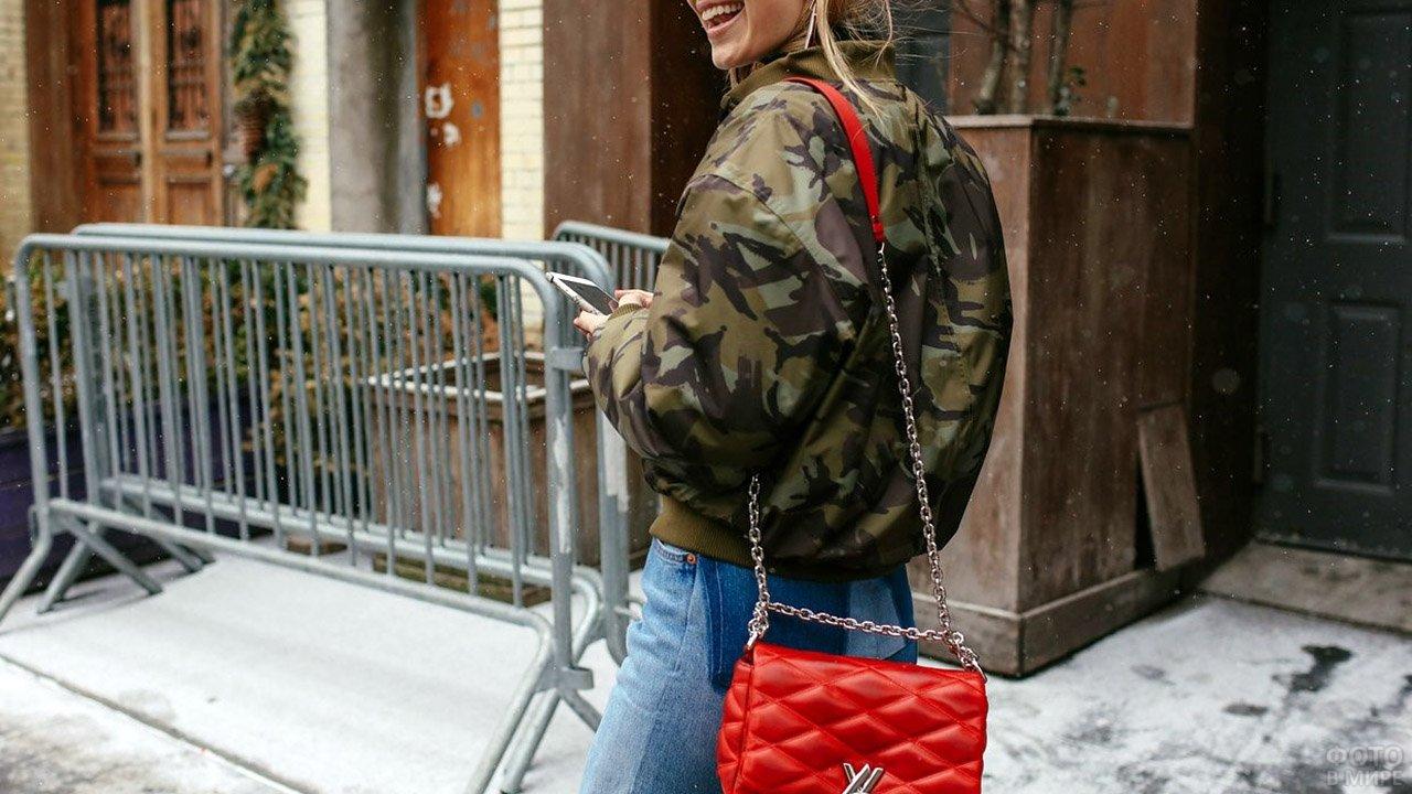 Девушка в куртке-бомбер камуфляжной расцветки с красной сумочкой