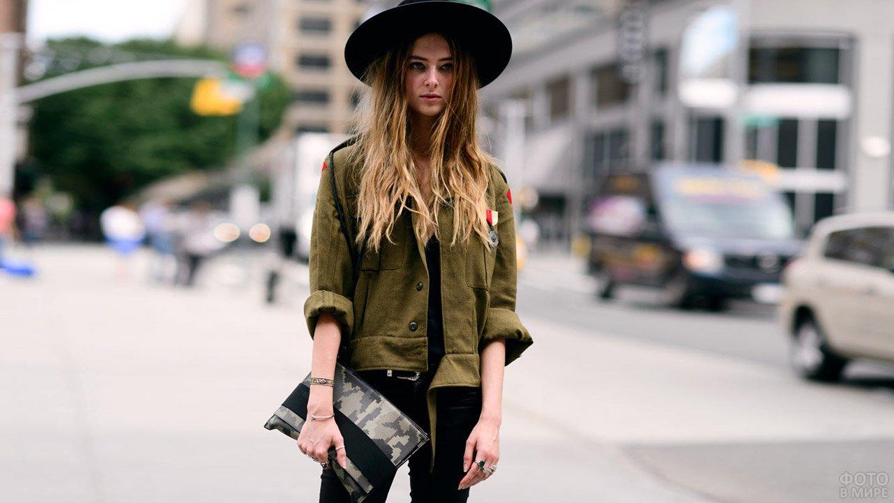 Юная девушка в куртке цвета хаки с сумкой-клатчем камуфляжной расцветки