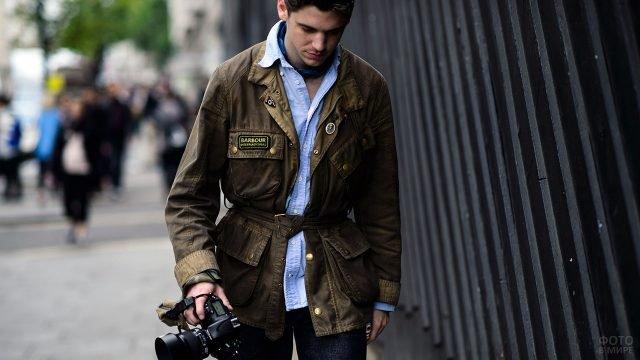 Юноша в милитари-куртке идёт по улице с фотоаппаратом в руках