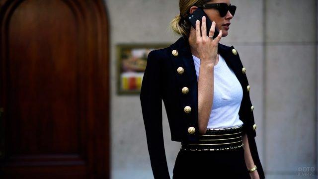 Женщина в строгом костюме в стиле милитари с золотыми пуговицами