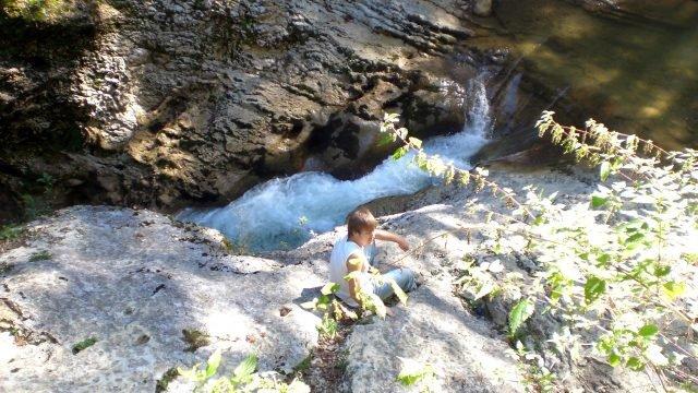 Молодой человек на скалистом берегу речки в Гуамском ущелье
