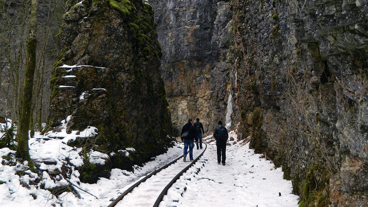 Туристы идут по снегу в Гуамском ущелье
