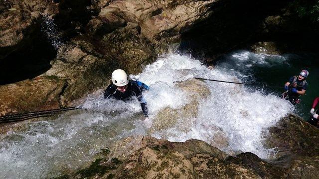 Туристы спускаются через поток реки в Гуамское ущелье