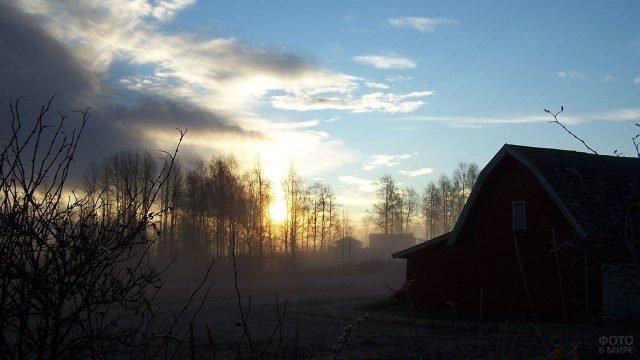 Солнце сквозь дымку в зимней деревеньке