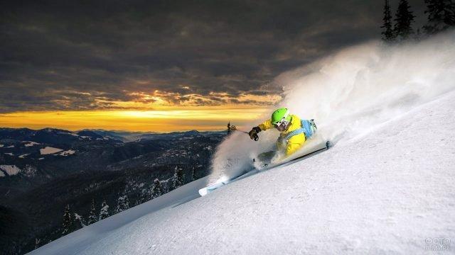 Горнолыжник на снежном склоне на фоне заката