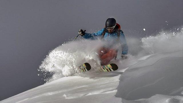 Горнолыжник вздымает фонтан снега