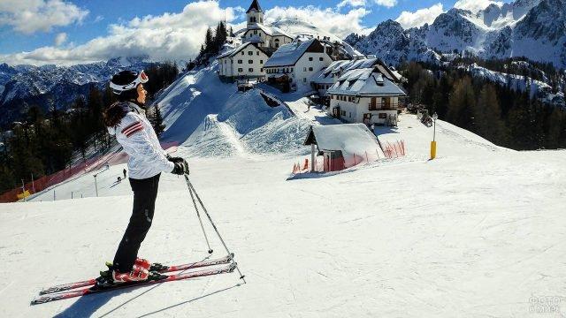 Лыжница в белой куртке на горнолыжном курорте