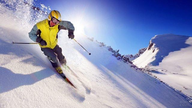 Лыжник-фрирайдер на фоне солнца в зените