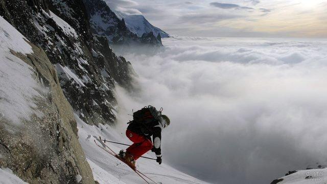 Лыжник-фрирайдер прыгает с горы в туман