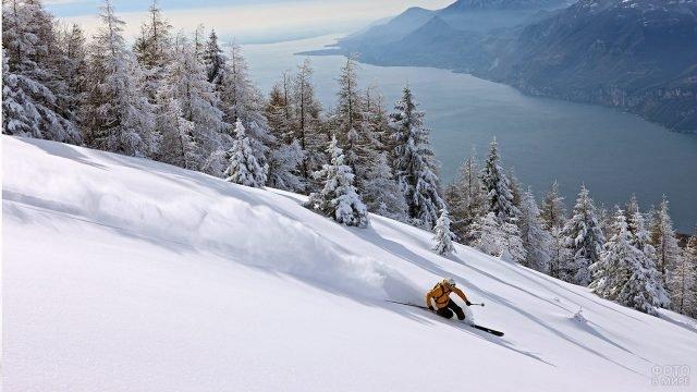Лыжник-фрирайдер в жёлтой куртке на заснеженном склоне горы над озером