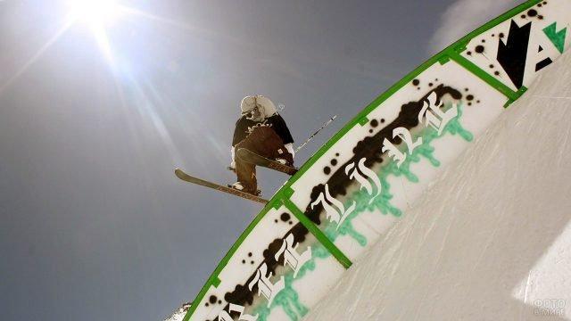 Лыжник-фрирайдер выполняет трюк, запрыгнув на ограждение