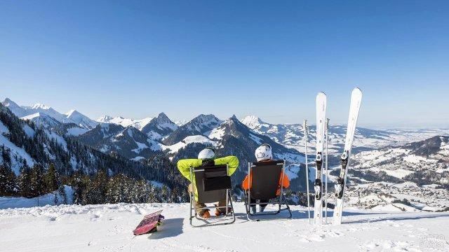 Лыжник и сноубордист отдыхают на вершине горы