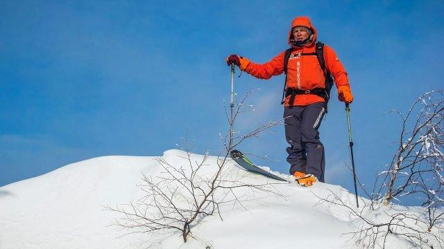 Лыжник на снежной вершине холма