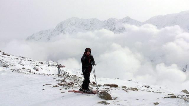 Лыжник на вершине горы на фоне подъёмника в тумане