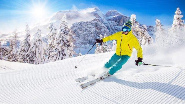 Лыжник на залитой солнцем горной трассе