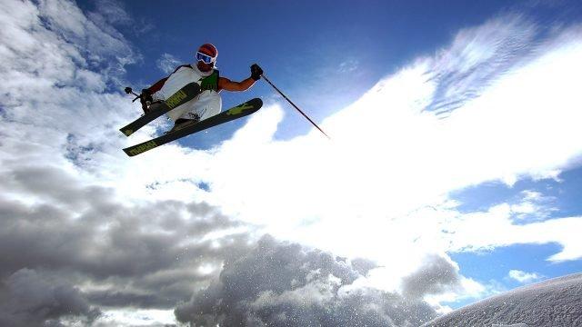 Лыжник в прыжке на фоне неба