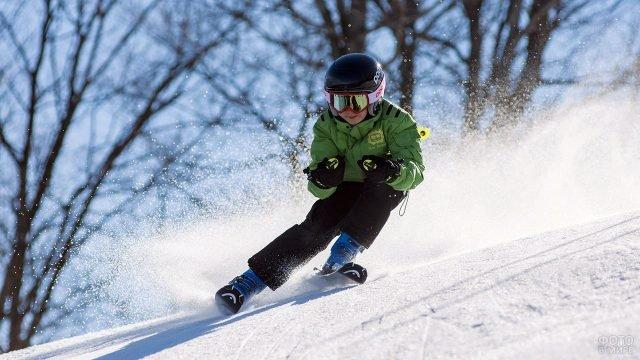 Мальчик мастерски спускается по горнолыжной трассе