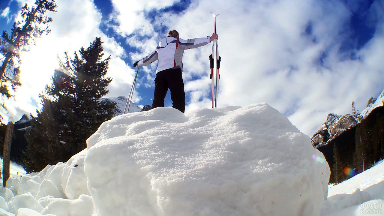 Счастливая лыжница на вершине снежного сугроба