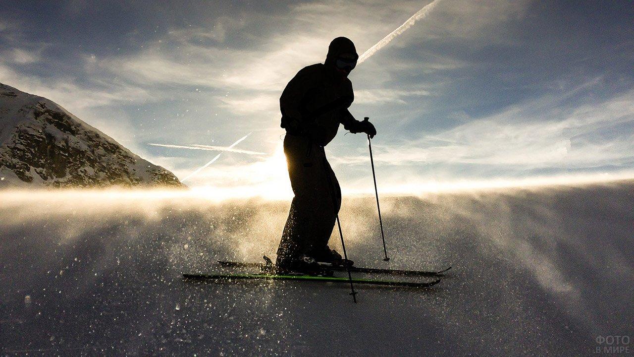 Силуэт лыжника на фоне заката в горах