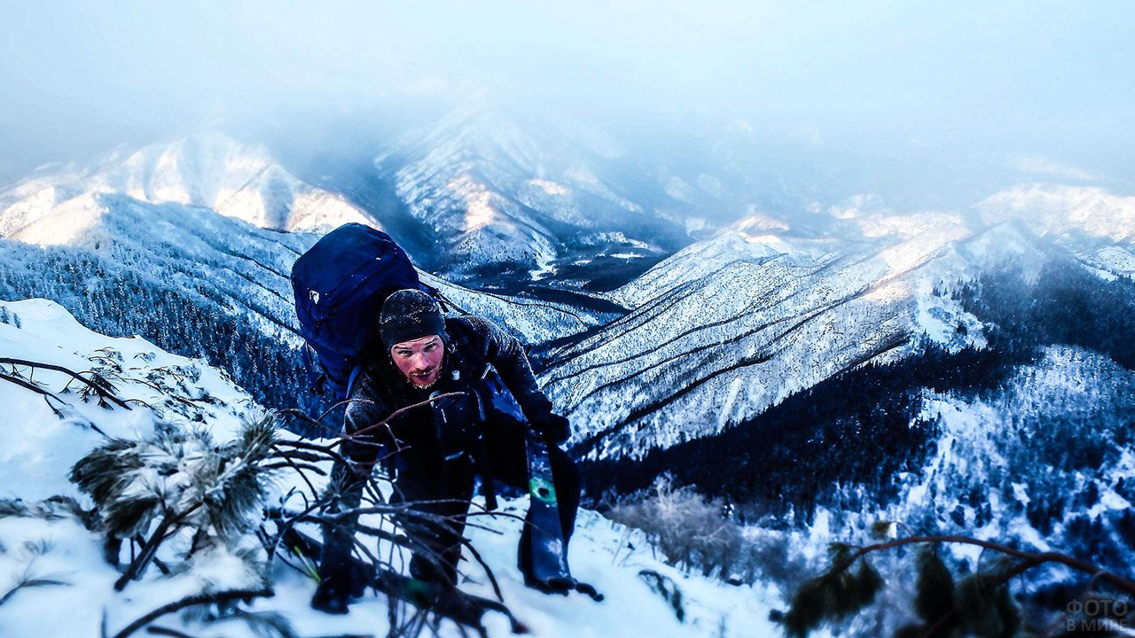 Турист с лыжами карабкается на вершину горы