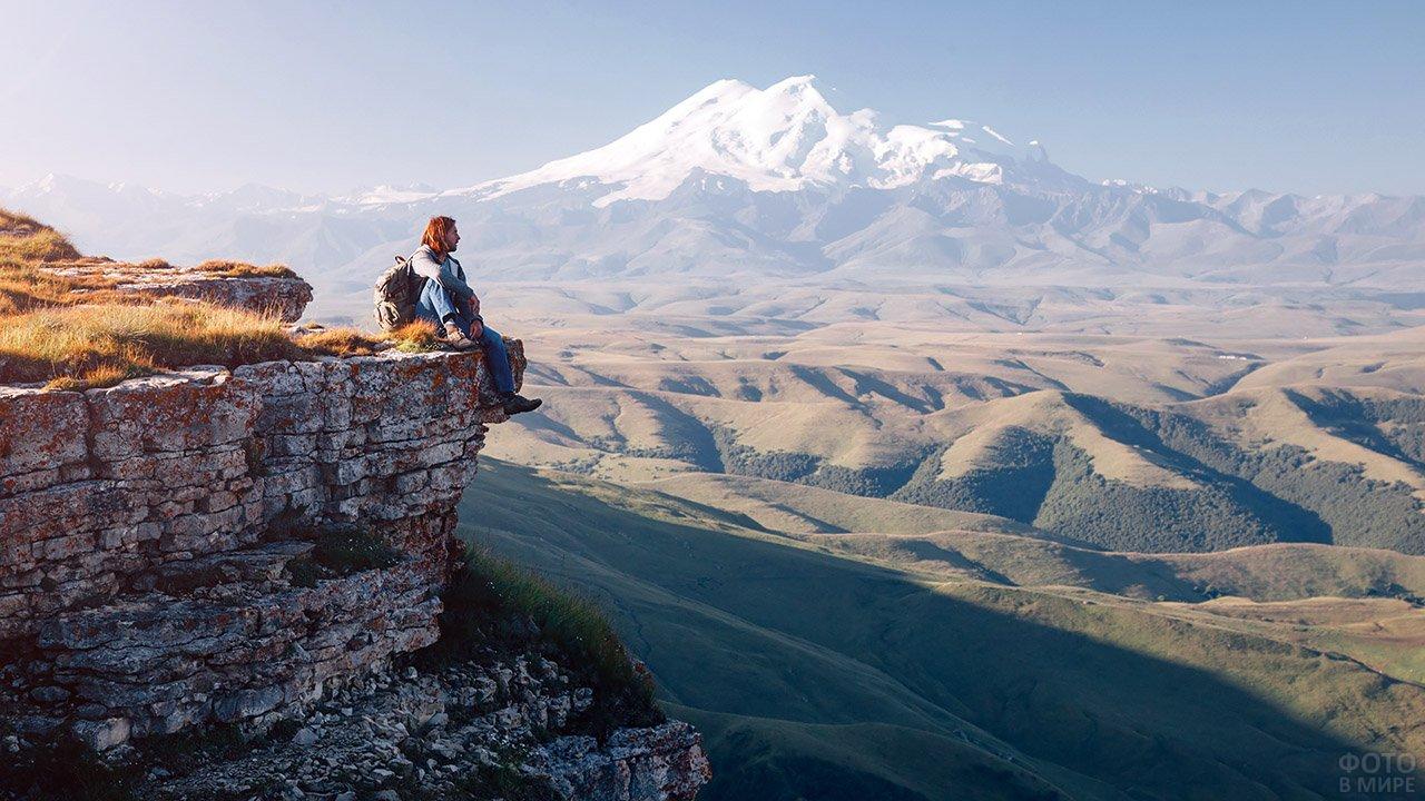 Турист с рюкзаком сидит на краю обрыва на фоне Эльбруса