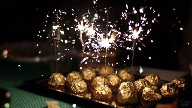 Бенгальские огни воткнутые в конфеты в коробке