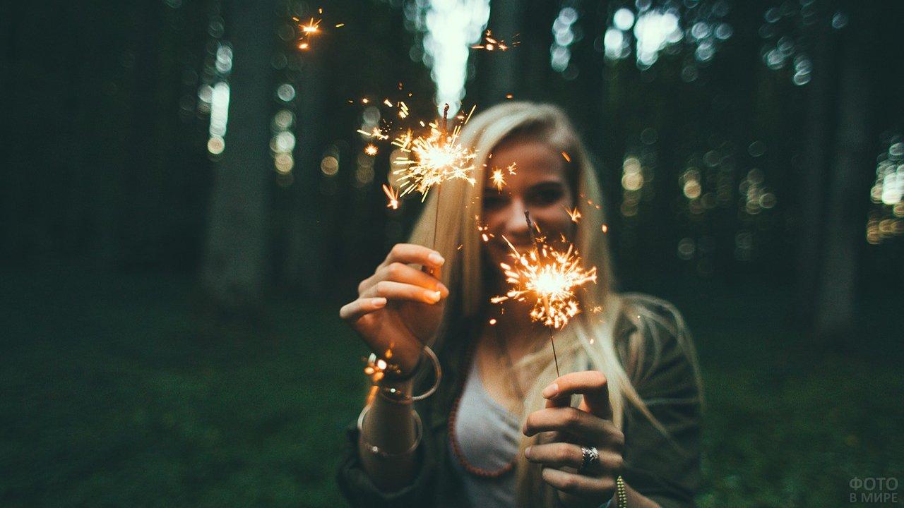 Блондинка в вечернем лесу с бенгальскими огнями в руках