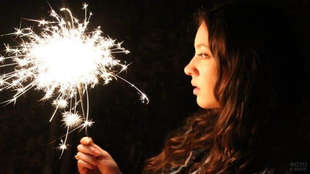 Девушка держит бенгальский огонь перед глазами