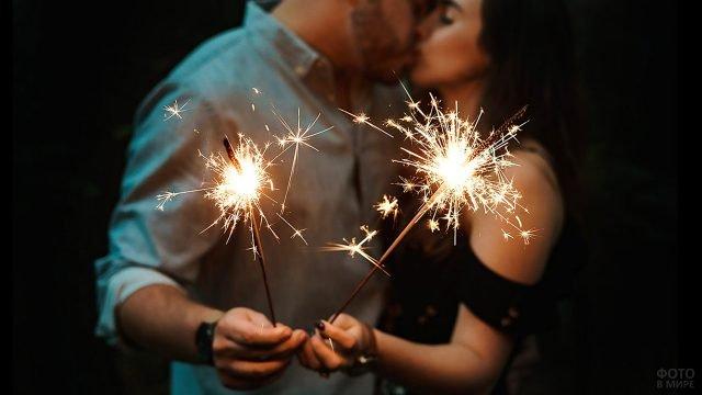 Два бенгальских огонька в руках целующейся парочки