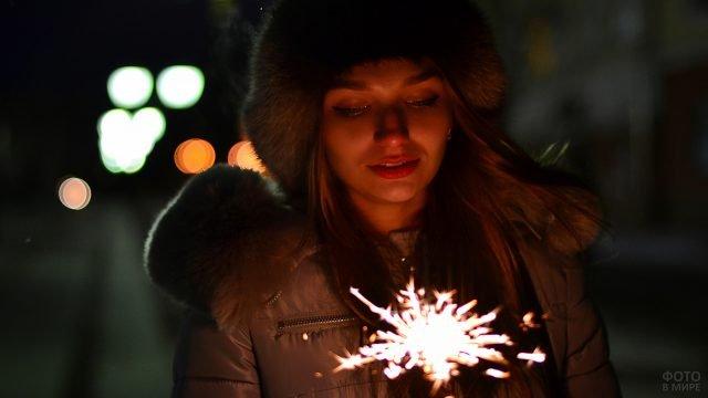 Красивая девушка в мохнатой шапке с бенгальским огнём на вечерней улице