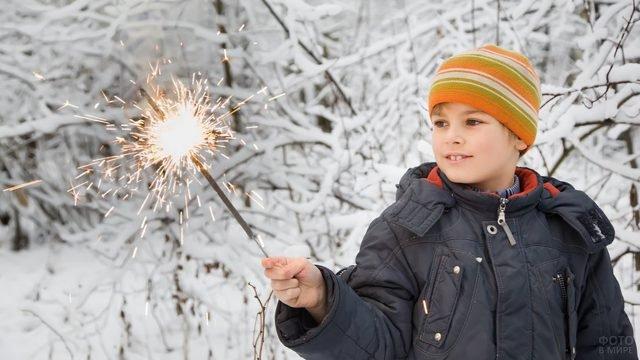 Мальчик на заснеженной улице держит в руках большой бенгальский огонь