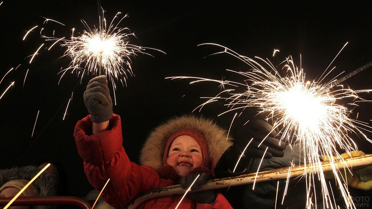 Малыш держит бенгальский огонь на вечерней улице