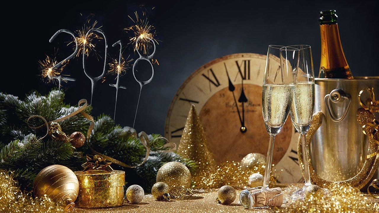 Новогодний натюрморт в золотых тонах с шампанским и бенгальскими огнями в форме числа 2018